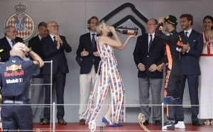 Princess Charlene drinks champagne offered by winning driver Daniel Ricciardo at the Monaco Grand Prix
